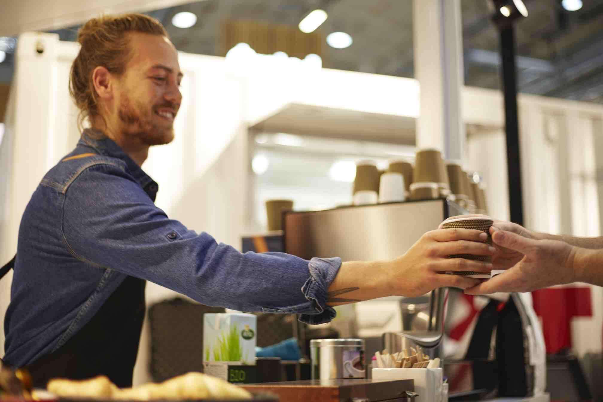 Barista reicht Kunden einen Kaffee